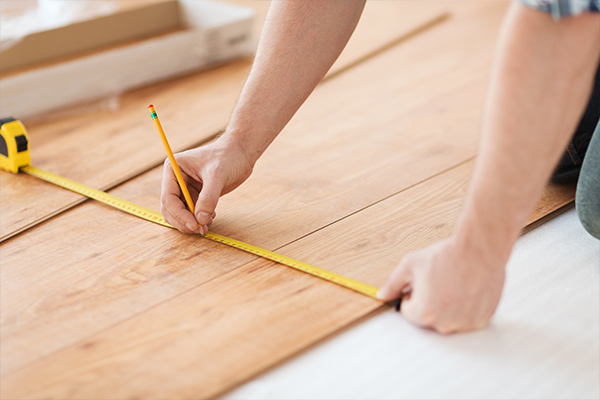 An image of a man fitting a wooden floor