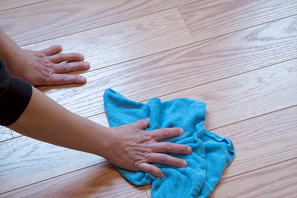 An image of a man cleaning a wooden floor