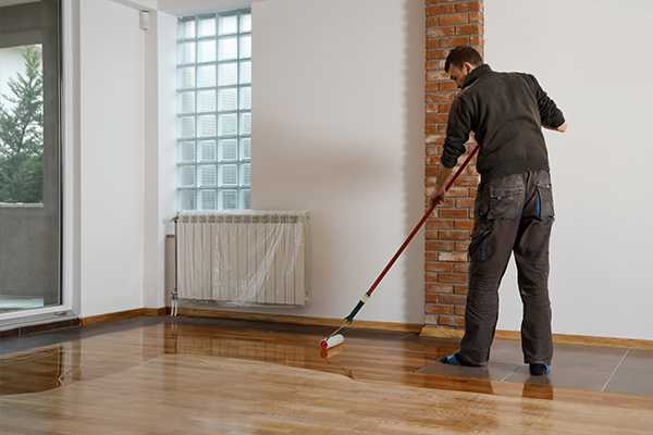 An image of a man applying sealant to a wooden floor